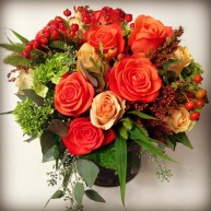 Orange roses, berries, hydrangea, grasses and eucalyptus.